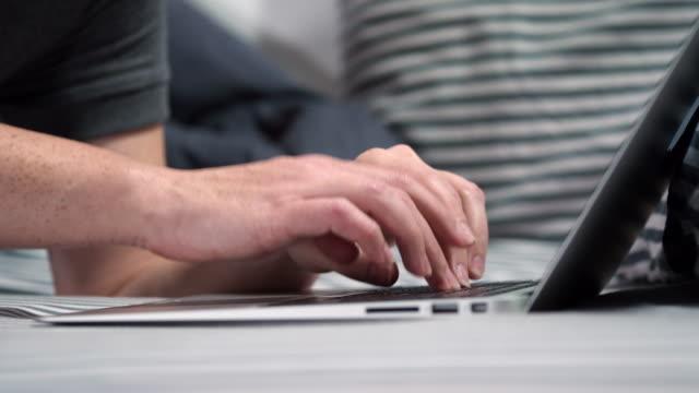 vidéos et rushes de femme utilisant l'ordinateur portatif dans le lit - hot desking