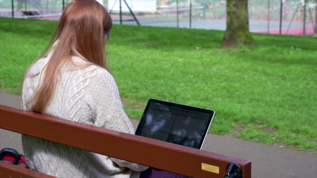 Woman Using Laptop In Park