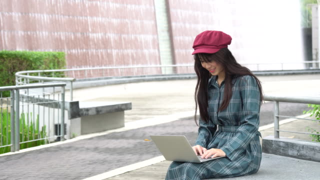 woman using laptop in public park - hot desking stock videos & royalty-free footage