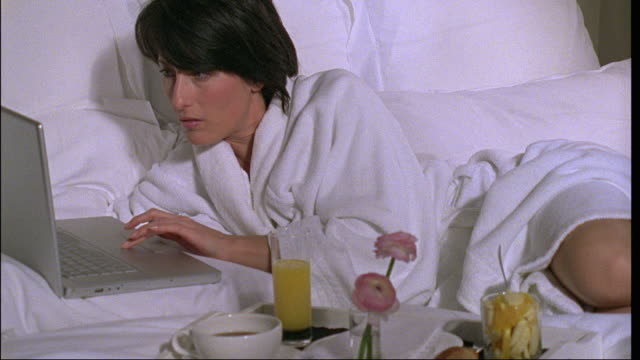 ms, woman using laptop lying next to breakfast tray in bed, brussels, belgium - hot desking stock videos & royalty-free footage
