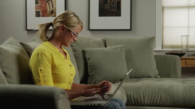 MS ZI Woman using laptop on sofa, holding credit card / Orem, Utah, USA