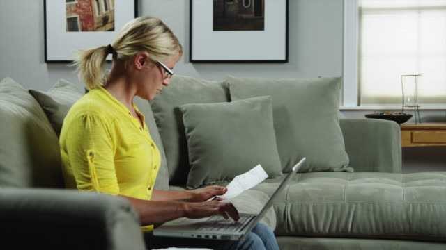 ms zi woman using laptop on sofa, holding document / orem, utah, usa - online banking video stock e b–roll