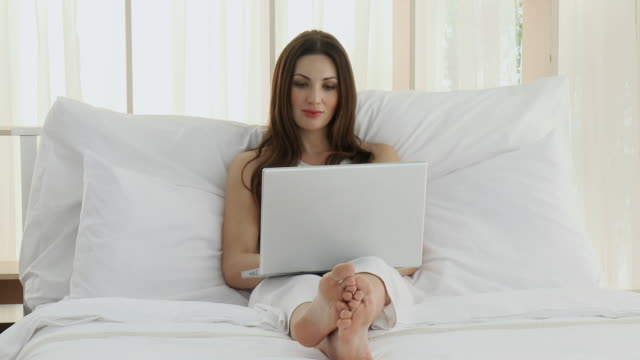 MS Woman using laptop sitting on bed / Cape Town, Western Cape, South Africa
