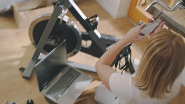 ms woman using laptop while assembling the exercise bike - adjusting stock videos & royalty-free footage