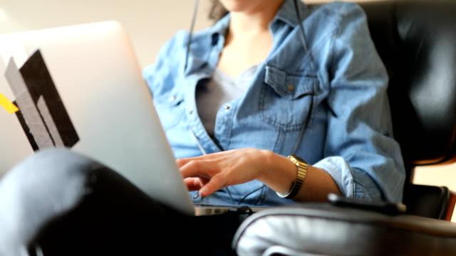 vidéos et rushes de femme à l'aide d'ordinateur portable tout en étant assis sur la chaise à la maison - assis en tailleur