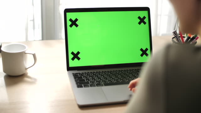 woman using laptop with green screen - over the shoulder stock videos & royalty-free footage