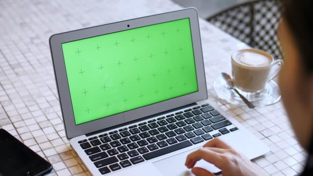 woman using laptop with green screen - modello dimostrativo video stock e b–roll