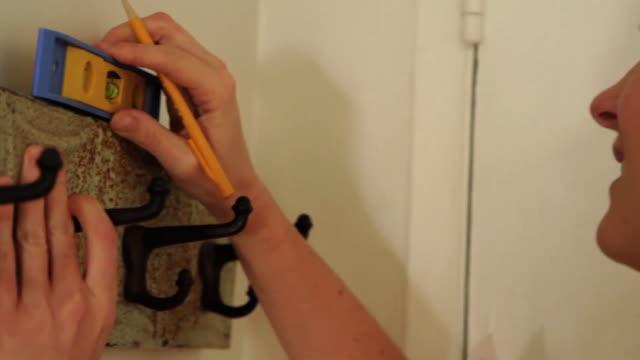 vídeos y material grabado en eventos de stock de cu woman using level to hang coat rack - colgador