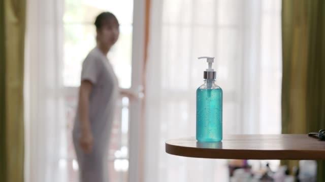 vídeos de stock e filmes b-roll de woman using liquid gel hand sanitiser to clean her hands - uma pessoa