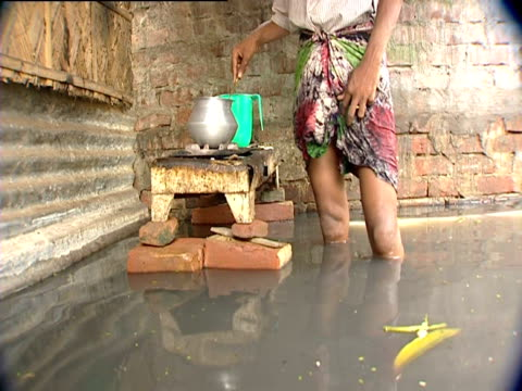 woman using makeshift stove propped up on bricks folowing severe floods - makeshift stock videos and b-roll footage