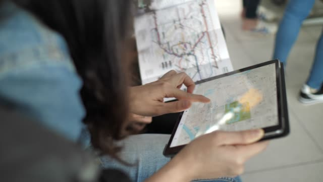 woman using map on digital tablet with friend - planning stock videos & royalty-free footage