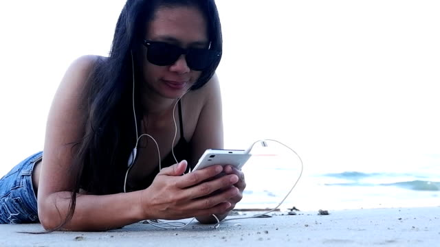 woman using mobile cell smart phone laughing on beach wearing earphones for music or talking girl in bikini using smartphone happy and listen to music. - oahu stock videos and b-roll footage