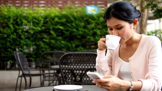 Woman using mobile phone and drinking coffee
