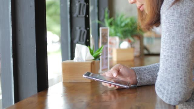 stockvideo's en b-roll-footage met vrouw met behulp van de mobiele telefoon en ontspannen aan koffie café, dolly schot - draagbaarheid