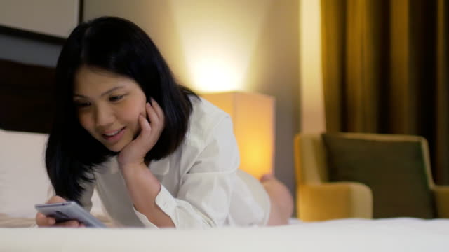 vídeos y material grabado en eventos de stock de mujer con teléfono móvil en el tiempo de descanso en el dormitorio - sólo mujeres jóvenes