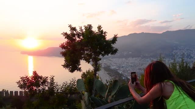 vídeos de stock, filmes e b-roll de mulher usando celular na hora do pôr do sol - só uma mulher madura