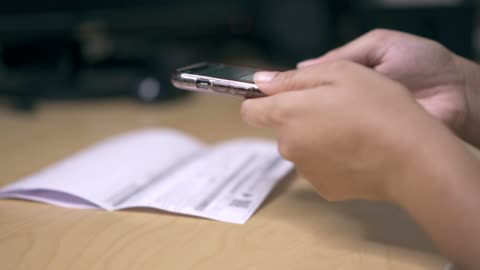 a woman using mobile phone for application qr code payment at home - document stock videos & royalty-free footage