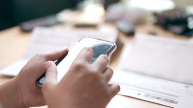 vidéos et rushes de une femme utilisant le téléphone mobile pour le paiement de code qr d'application à la maison - financial bill