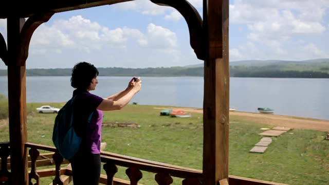 woman using mobile phone for photography on the lookout tower