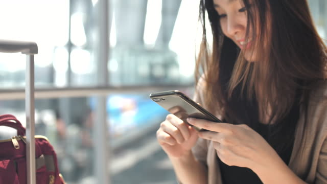 woman using mobile phone in airport - gate stock videos & royalty-free footage
