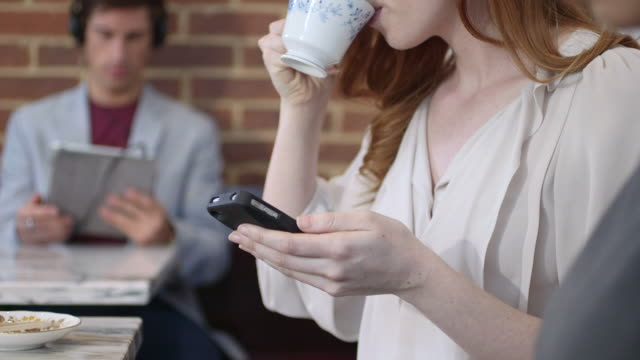 woman using mobile phone in coffee shop - greater london stock videos & royalty-free footage