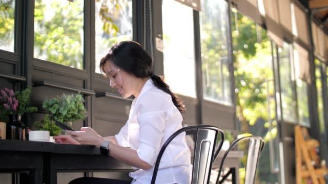女性コーヒー カフェで携帯電話を使ってスローモーションします。 - カフェ点の映像素材/bロール