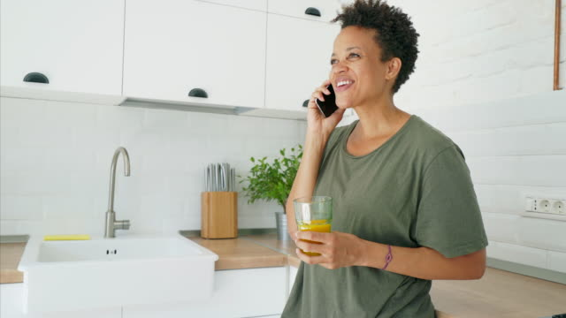 Woman using mobile phone in the kitchen.