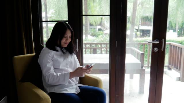 女性のリラックス時間を自宅で携帯電話を使用して - 椅子点の映像素材/bロール