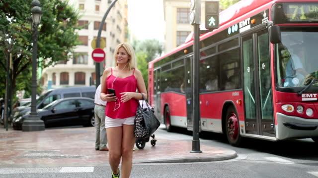 Vrouw met behulp van mobiele telefoon in stedelijke omgevingen: bij stoplicht