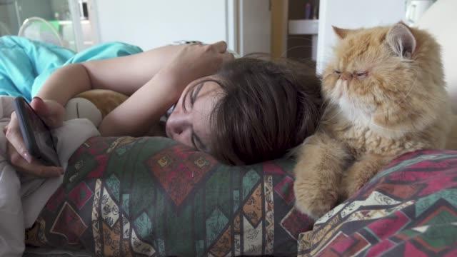 ベッドで彼女の脂肪質猫のかわいい携帯電話をしている女の人 - photographing点の映像素材/bロール