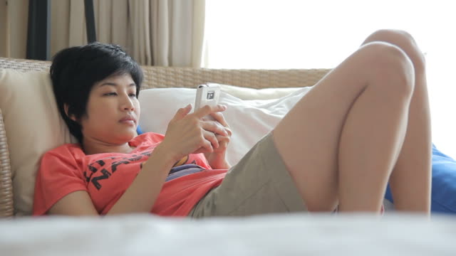 vídeos de stock, filmes e b-roll de hd: mulher usando o telefone celular no sofá - reclining