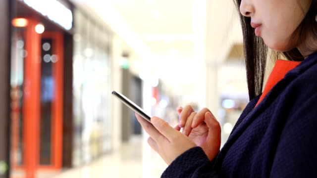 Woman using mobile phone online in mall