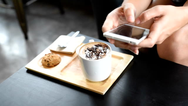 woman using mobile phone while drink coffee - coffee drink stock videos & royalty-free footage