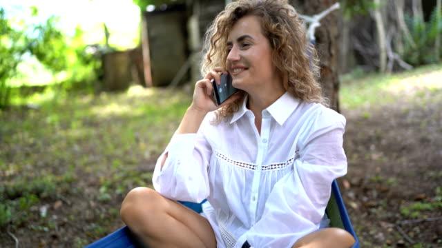 vídeos de stock e filmes b-roll de woman using mobile phone while relaxing in a hammock - corda