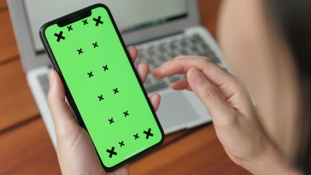 vídeos de stock, filmes e b-roll de mulher usando telefone celular com tela verde, vertical - rolando