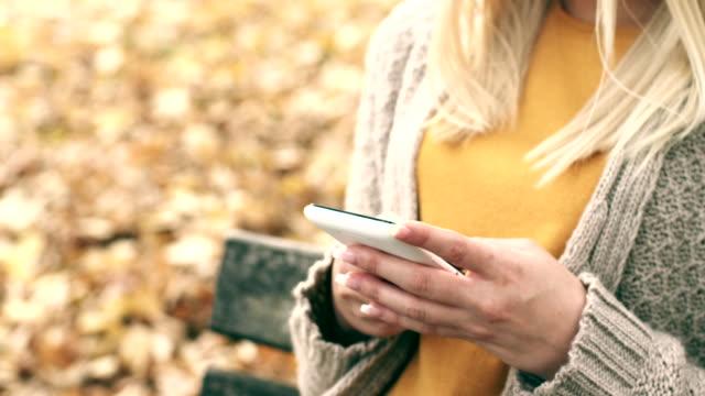 vídeos y material grabado en eventos de stock de mujer mediante teléfono móvil inteligente al aire libre - un solo objeto