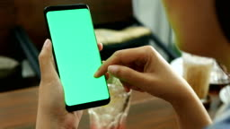 4K. woman using mobile smartphone with blank green screen mock-up at coffee shop, use finger touch on screen and slide , swiping, scrolling gestures.