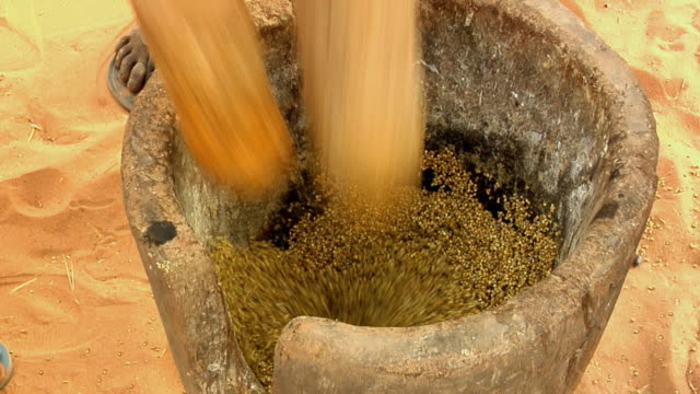 cu, woman using mortar and pestle for grinding millet grain, low section, niamey, niger - ニアメ点の映像素材/bロール