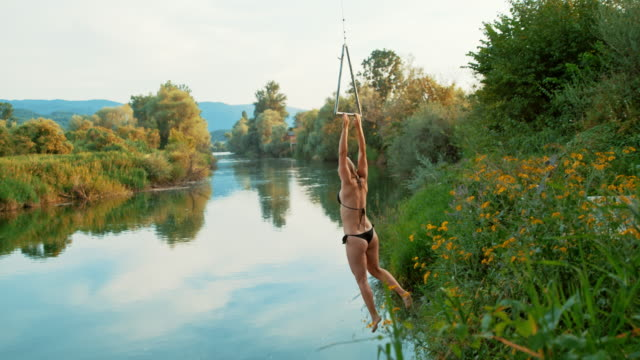 super slo mo super slo mo woman using on a rope swing to jump into the river - rope swing stock videos & royalty-free footage