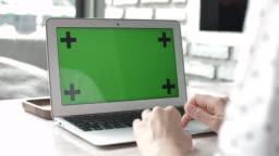Woman using on laptop with green screen