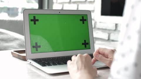 stockvideo's en b-roll-footage met vrouw met behulp van op laptop met groen scherm - over shoulder