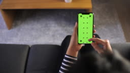 Woman using on smart device with Green screen