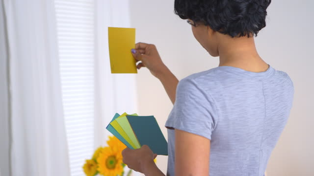 woman using paint chips to pick out color for room