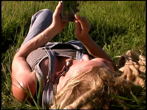 woman using pda in grassy field - electronic organiser stock videos & royalty-free footage
