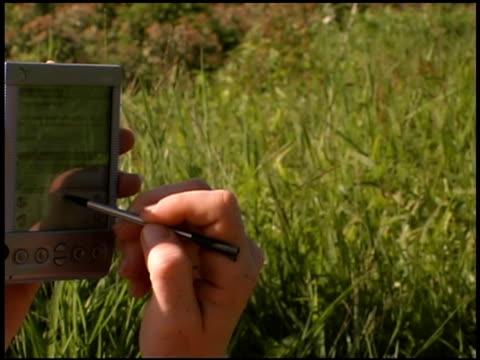 woman using pda in grassy field - einzelne frau über 30 stock-videos und b-roll-filmmaterial