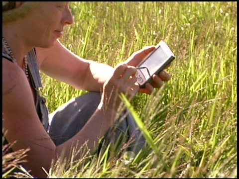 woman using pda in grassy field - dreiviertelansicht stock-videos und b-roll-filmmaterial
