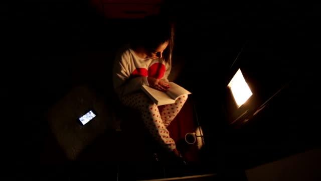 stockvideo's en b-roll-footage met vrouw met behulp van de telefoon en het lezen van een boek - open haard