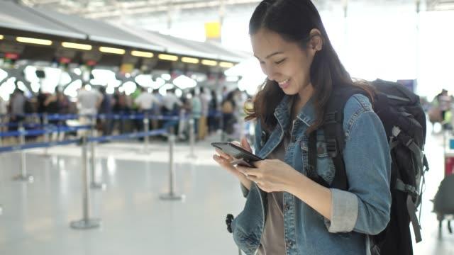 vídeos y material grabado en eventos de stock de mujer con el teléfono en el aeropuerto - pasajero