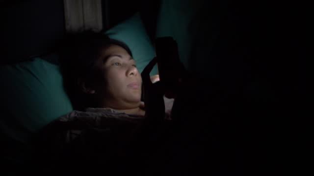 SLO MO Woman using phone at night
