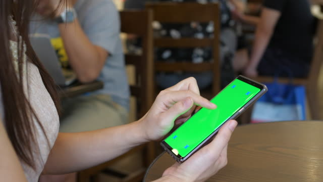 vídeos de stock, filmes e b-roll de mulher usando a tela do telefone verde - espaço vazio